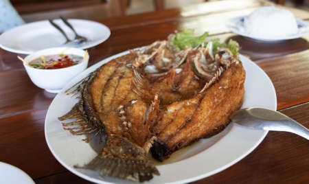 deep fried crispy sea bass with fish sauce on white plate in restaurant