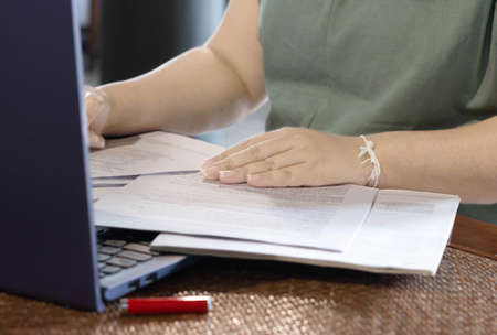 woman's hand on paperwork represent working in office or home