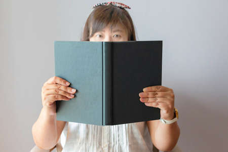 blurred asian female face holding and looking at book for reading template Stock Photo