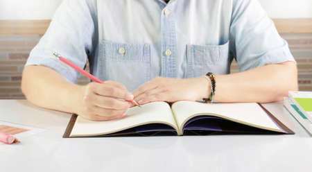 hand holding pencil writing notebook on desk in classroom Stock Photo