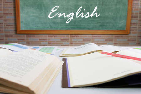 white writing English text on blackboard in front of blurred textbooks on table in classroom
