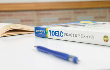 NAKHON RATCHASIMA, THAILAND- August 9, 2020: Barron's Toeic book on white table with textbook and pen in classroom