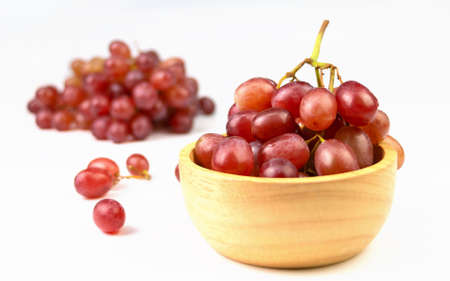 red grapes in wooden cup on white background Stock Photo