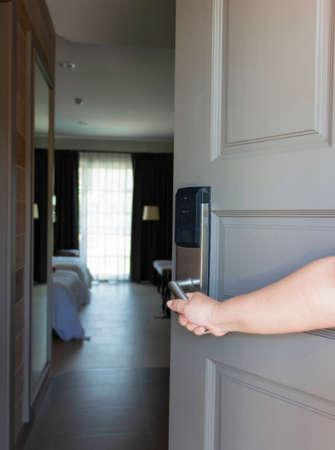 hand holding electronic door handle to open hotel room
