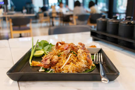 crispy crabs pad thai in black plate on white table in restaurant with blurred customers