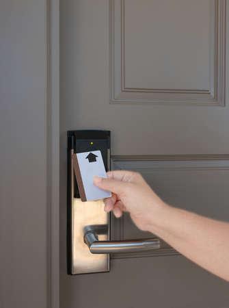 hand holding keycard to scan electronic lock door in order to open the door