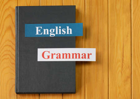 English cards on textbook on wooden board with copy space