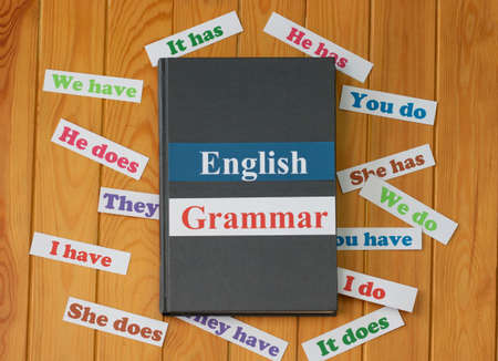 English cards on textbook surrounded by English grammar cards on wooden board Archivio Fotografico