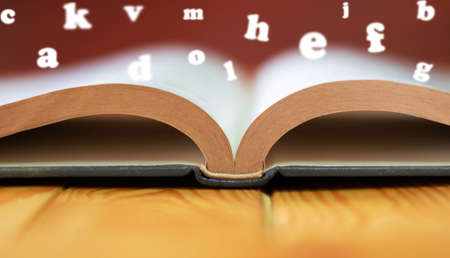 close up textbook on wooden table with copy space and blurred English alphabets floating over book page