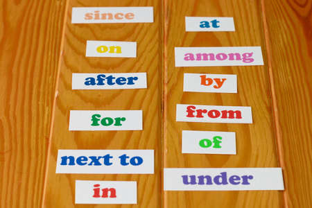 Colorful English preposition cards on wooden table