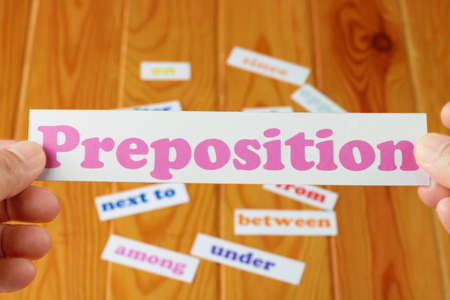 Hand holding English preposition card over blurred preposition words on wooden table