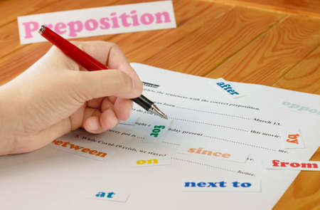 English preposition work sheet on wooden table with colorful English word cards Archivio Fotografico