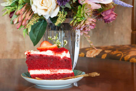 a slice of red strawberry velvel cheese cake on wooden table in vintage coffee shop