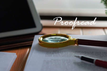 magnifier on blurred proofreading paper with proofread text floating above on wooden table nearby window in office Archivio Fotografico
