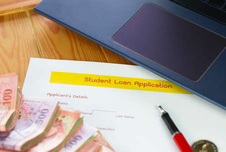 close up student loan application form on wooden table with banknotes and laptop