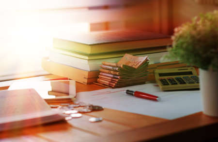 banknotes and books on wooden table with blurred coins and paperwork for school scholarship application concept