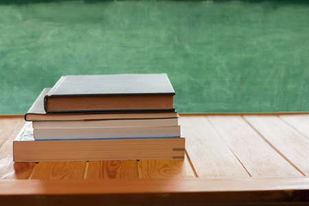 textbooks on wooden table in front of blurred blackboard represent concept of studying in classroom
