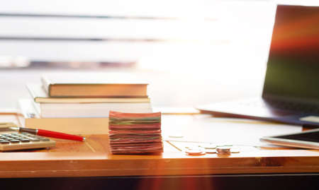 stack of cash on wooden table with blurred books and laptop nearby the window