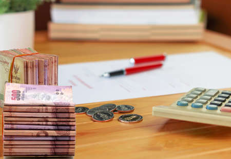 stack of banknotes and coins with calculator and blurred books on wooden table  represent cost of education 스톡 콘텐츠