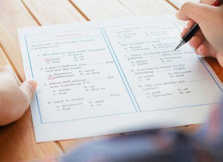 English grammar sheet on wooden table
