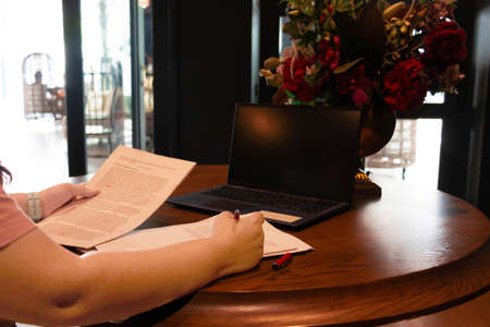 hand holding red pen over blurred paperwork on wooden table with laptop