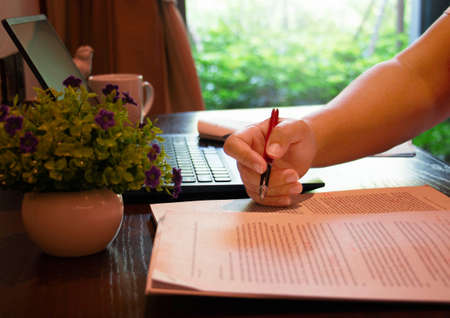 hand holding red pen over blurred paperwork on wooden table