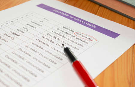 English grammar test sheet with red pen and clock on wooden table in classroom