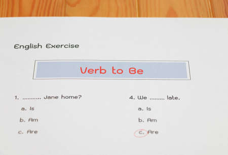 English grammar test sheet on wooden table in classroom