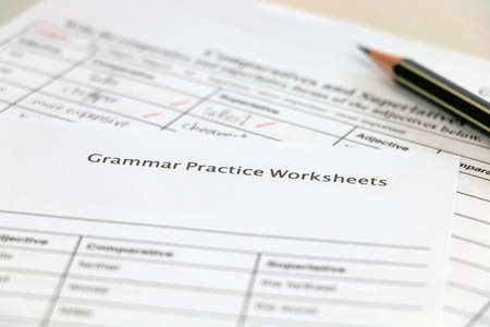 English grammar practice sheet with handwriting on white table