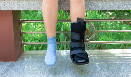 boot support on womon's leg to support her injured ankle from accident