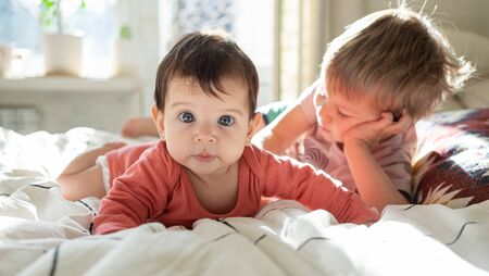 Little cute baby infant lying on the bed together with her toddler brother