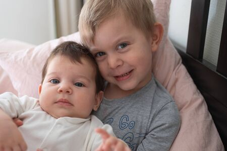 Toddler boy brother holding his newborn baby sister, sitting on the bed. Lifestyle