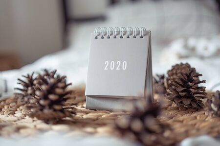 New Year 2020 grey calendar with lights on rustic server with cones and wooden Christmas tree toys