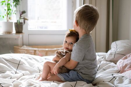 little infant baby girl sitting together with her toddler brother