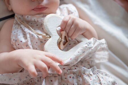 Little baby infant hands holding wooden rustic heart. selected focus. St. Valentines day concept