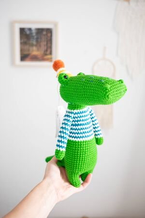 hand holding Crochet amigurumi toy crocodile for baby