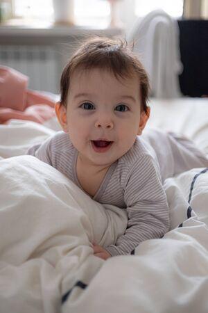 Poco lindo retrato de bebé infantil en ropa de género neutro sonriendo
