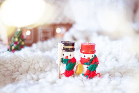 Little wooden snowmen and gingerbread house with lights. Christmas decorations