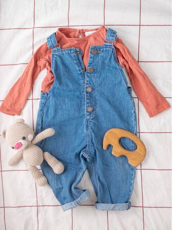 Baby denim jumpsuit with knitted hat and pink t-shirt, crochet teddy bear on white bed. Fashion baby clothes and accessories. Flat lay, top view.