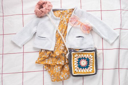 Mustard baby romper with knitted sweater and accessories with wooden toy and sunglasses