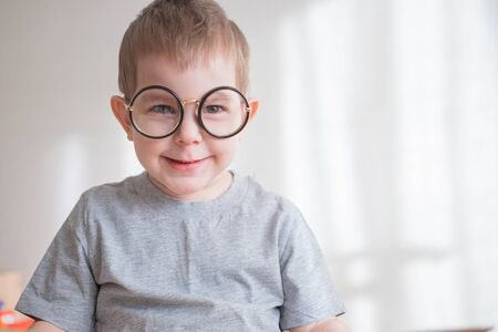 Little cute toddler preschooler boy in glasses with book looking straight at camera. Back to school concept Zdjęcie Seryjne
