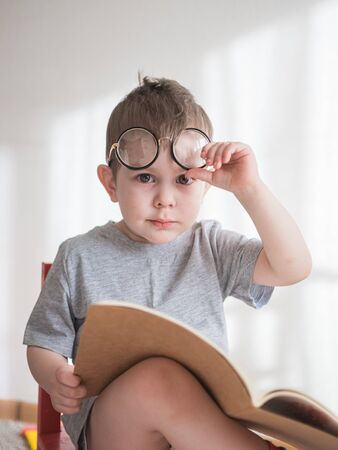 Cute toddler boy reading a book in glasses. Smart preschooler. Back to school concept