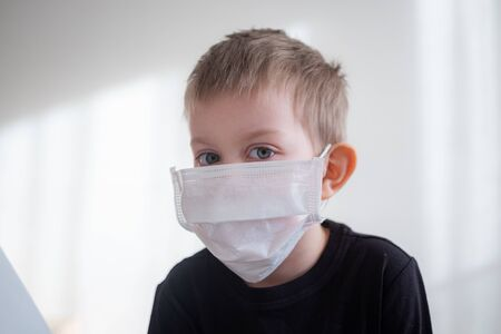Toddler boy portrait in white medical mask on white background. Coronavirus protection concept. quarantine home isolation