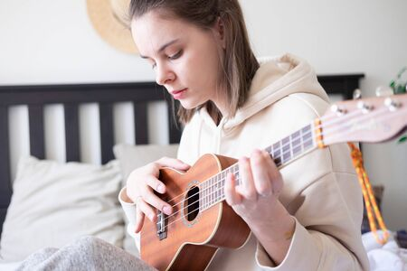 Close up portrait of young woman playing ukulele guitar at home. Spending time at home self-isolation quarantine