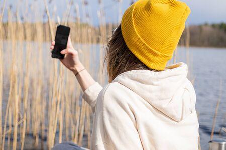 woman taking selfie, making video chat via smartphone outdoors near lake shore. No face portrait, faceless Фото со стока