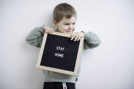 Toddler boy holding a felt letter-boad written Stay home. Stay home because of quarantine and self isolation. Social distancing.