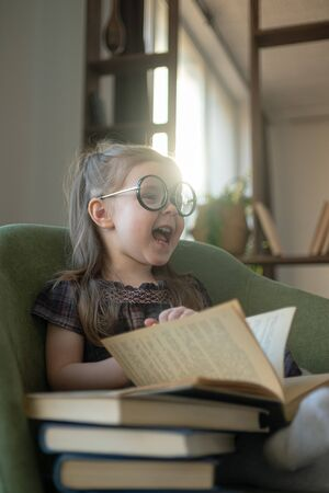 Little cute toddler girl in glasses reading books. back to school Stockfoto