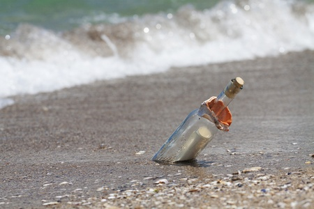 deserted: Message in a bottle with a wave coming. Horizontal shot with shallow depth of field.