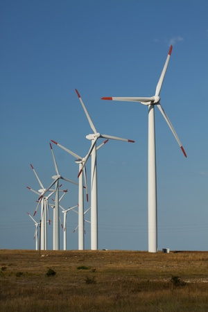 molino viento: Serie de generadores de energía eólica en un campo de hierba. Tiro vertical con fondo claro cielo azul. Foto de archivo