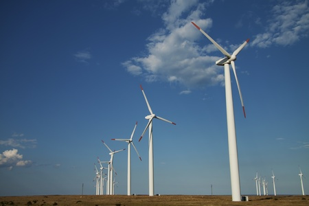 Series of wind power generators. Horizontal shot with blue sky and clouds in the background.